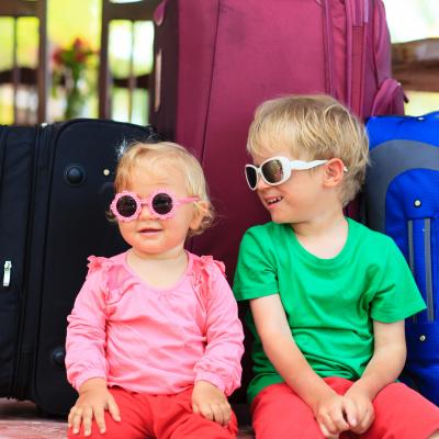 kids sitting on suitcases ready to travel